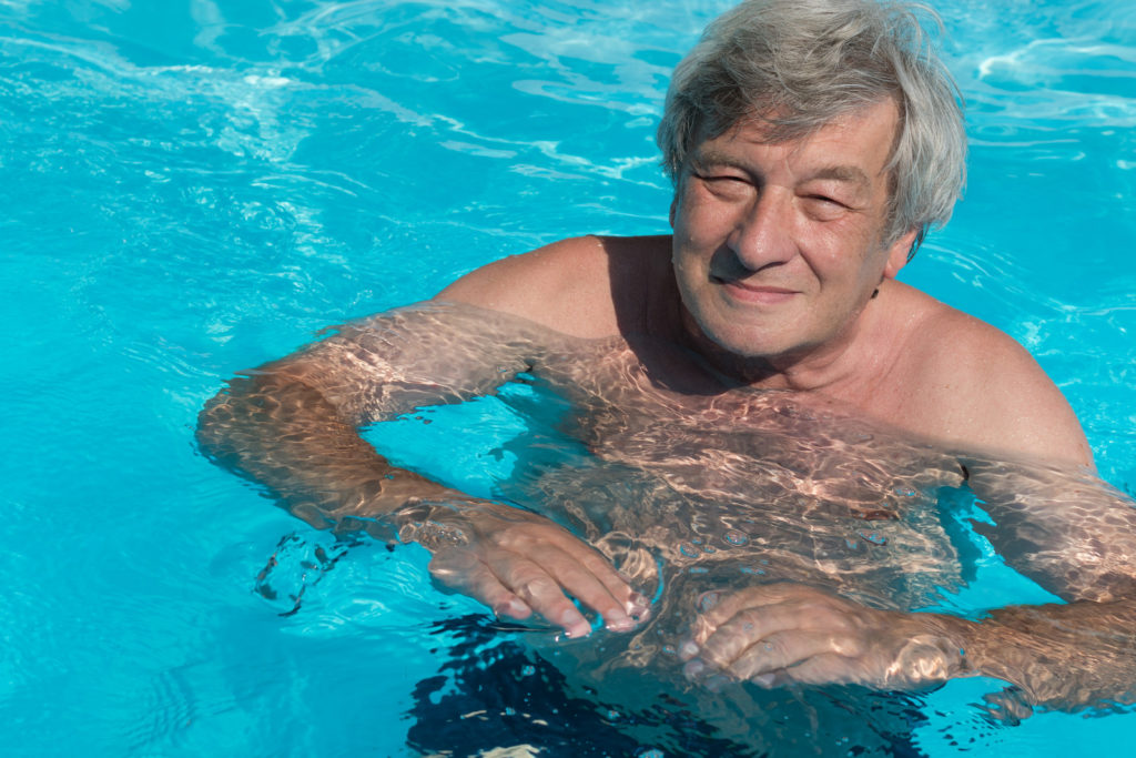 Senior man swims in a pool.