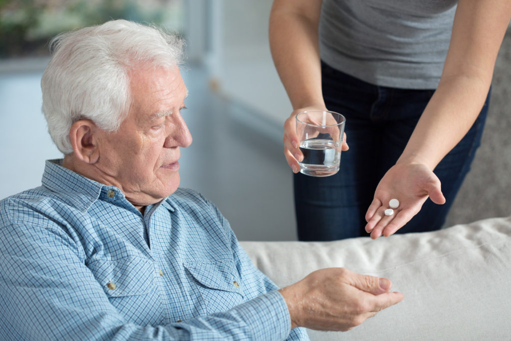 Senior man taking pills with water.