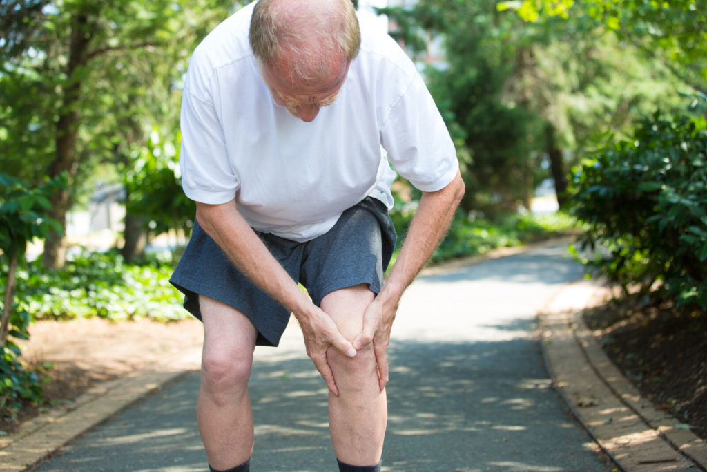 A senior man walking outside holds his knee in pain.