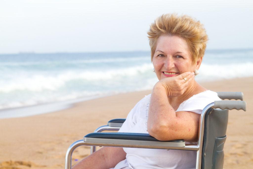 A senior woman sits on the beach inn a wheelchair.