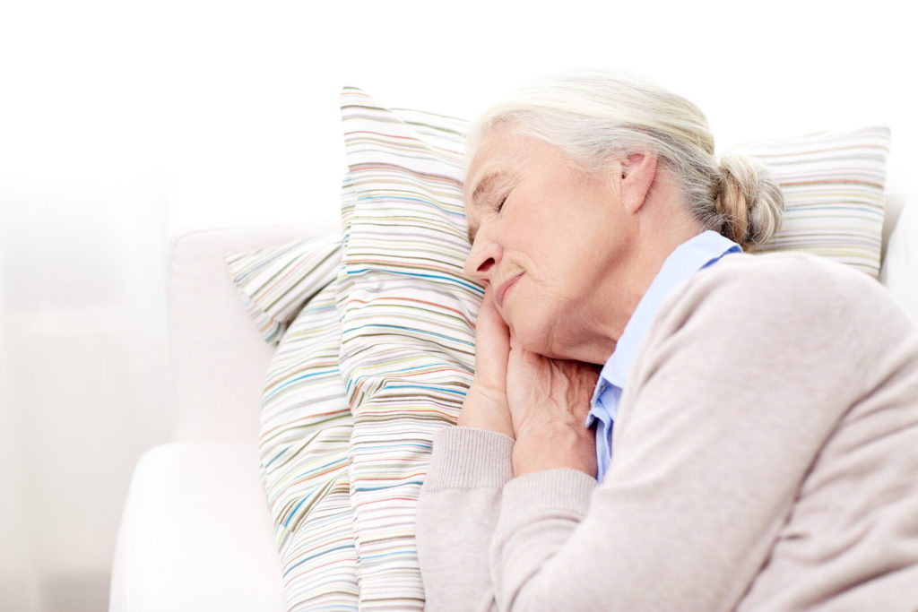 A senior woman sleeps on her side on top of two pillows.