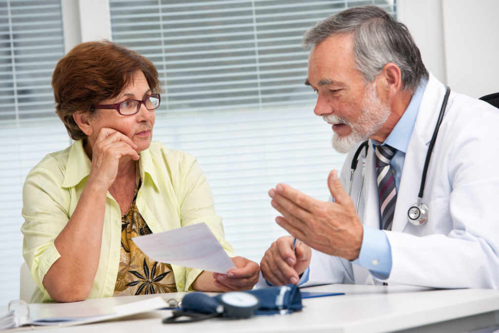 A senior woman talks to her doctor.