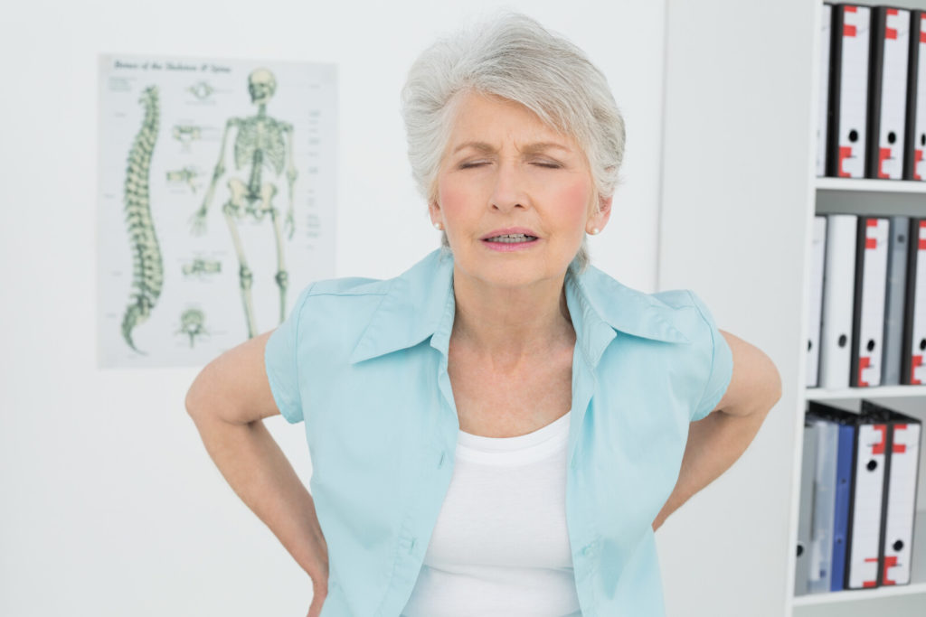 A senior woman has visible back pain as she waits in a doctor's office.