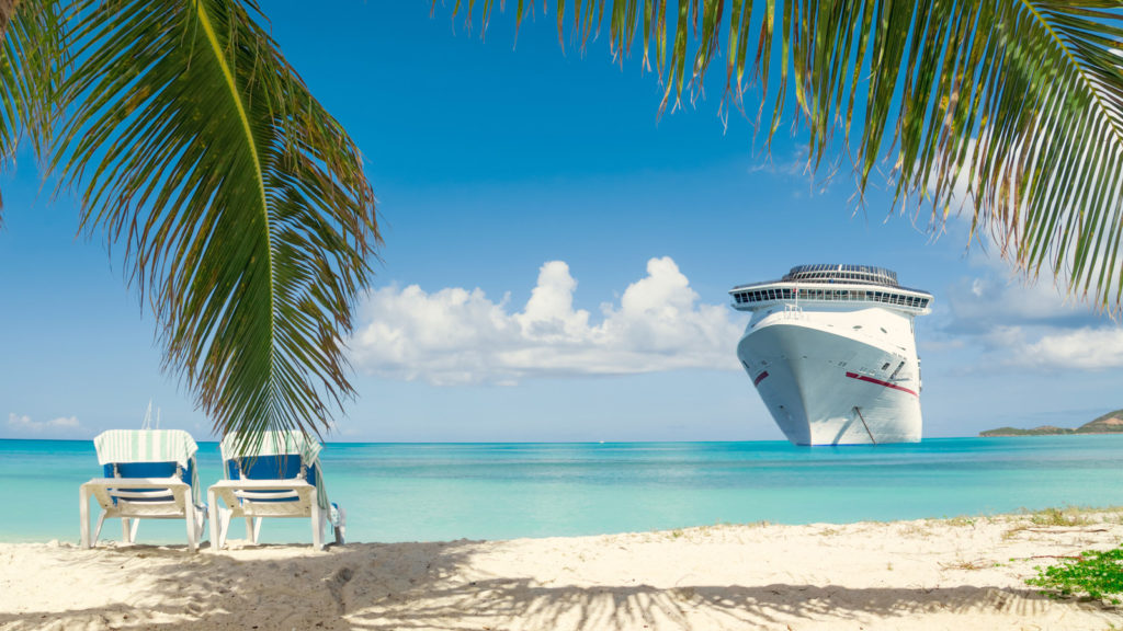 A beautiful tropical location has a cruise ship in the background on blue water.