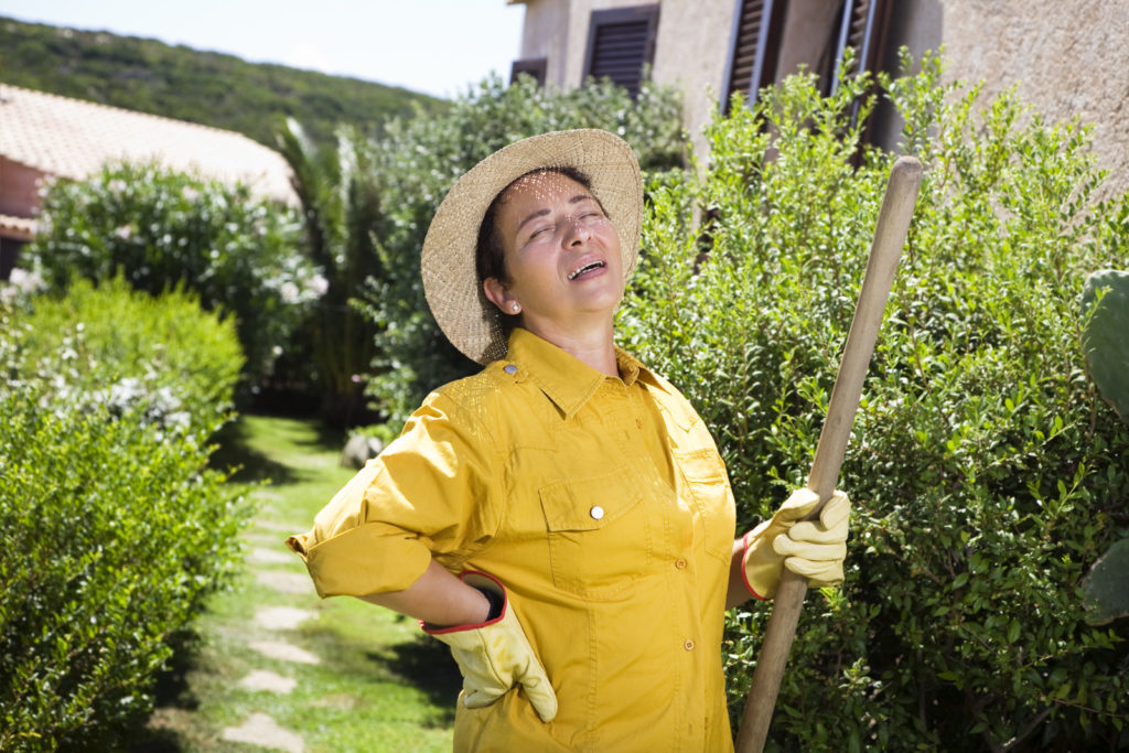 A woman gardening experiences back pain.