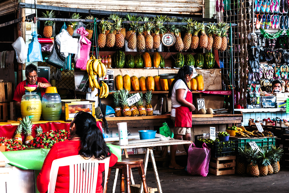 A Mexican Market with fresh fruit and a handful of people