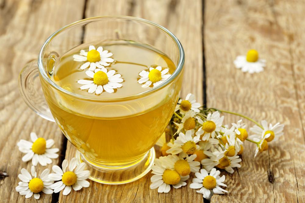 A mug of chamomile tea with chamomile flowers