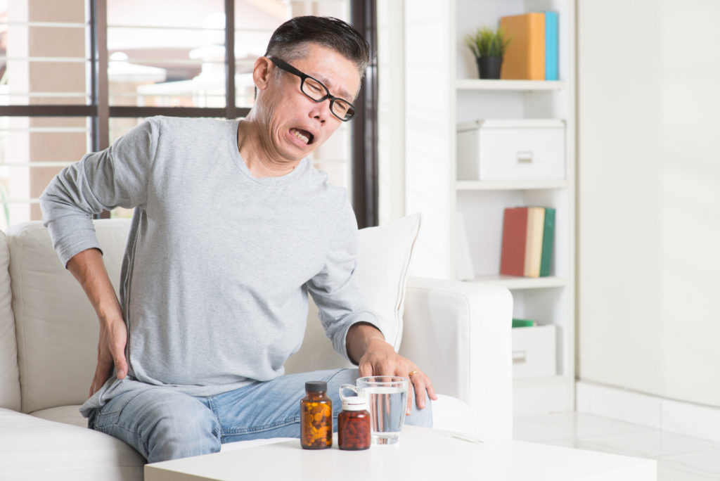 A senior man sitting has obvious hip pain.