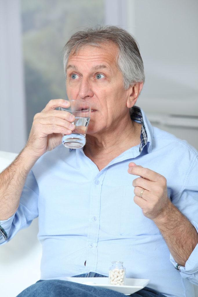 A senior man takes medication.