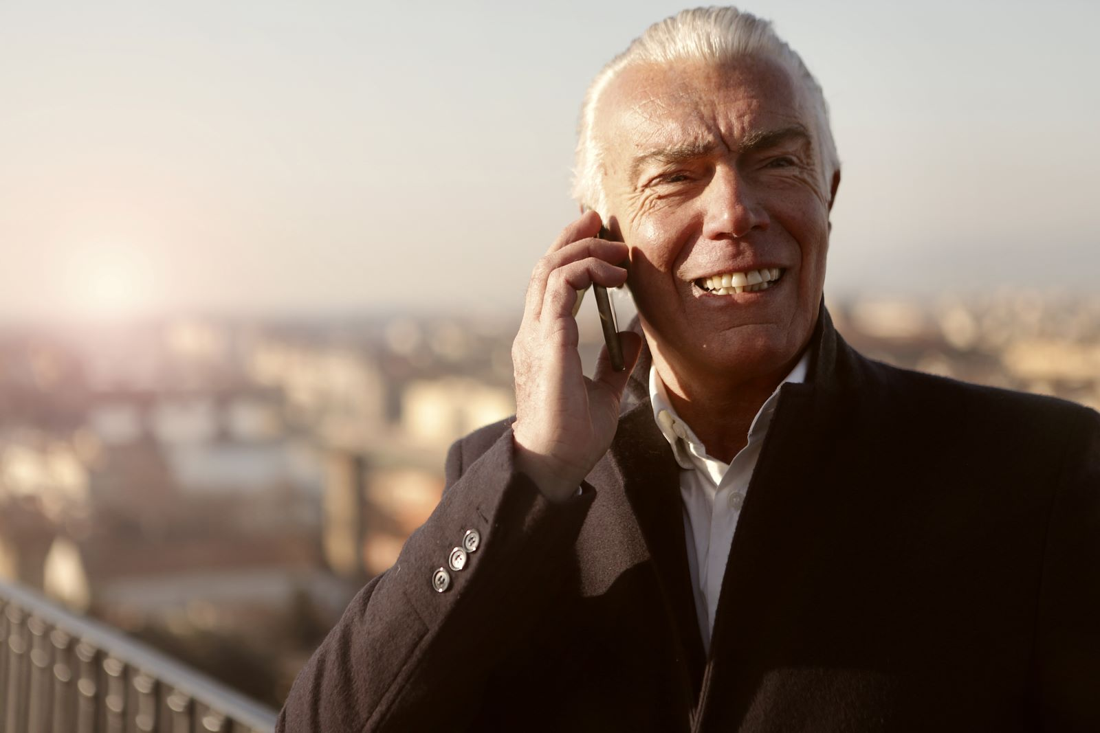 Cell Phone Plan Discounts for Seniors - Senior man in black jacket standing outside talking on cell phone with a blurred-out background of a city