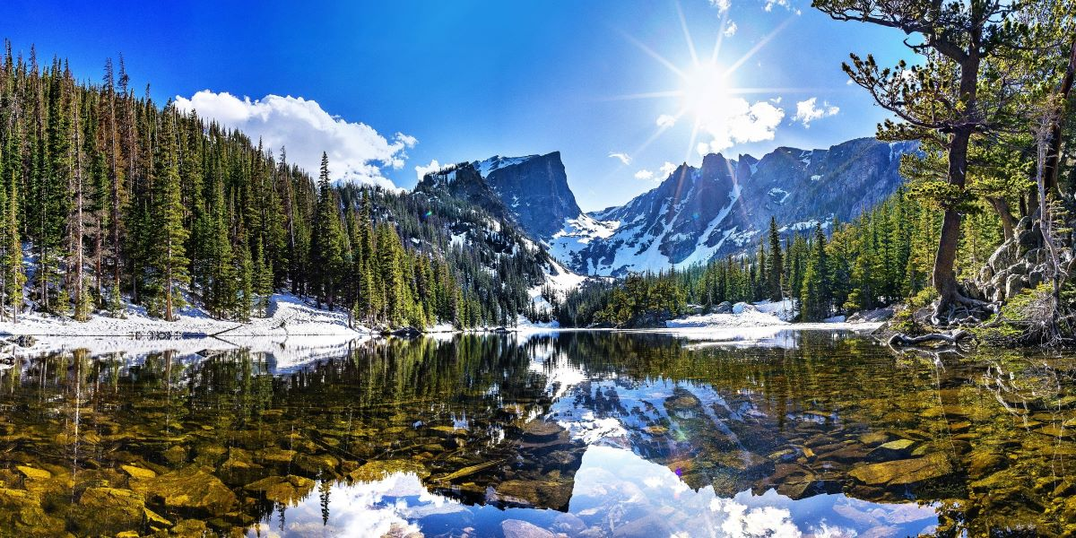 Best Places to Retire in Colorado - A crystal clear lake at the base of the mountain surrounded by pines and the mountain in the background, Blue skies with a few white billowy clouds