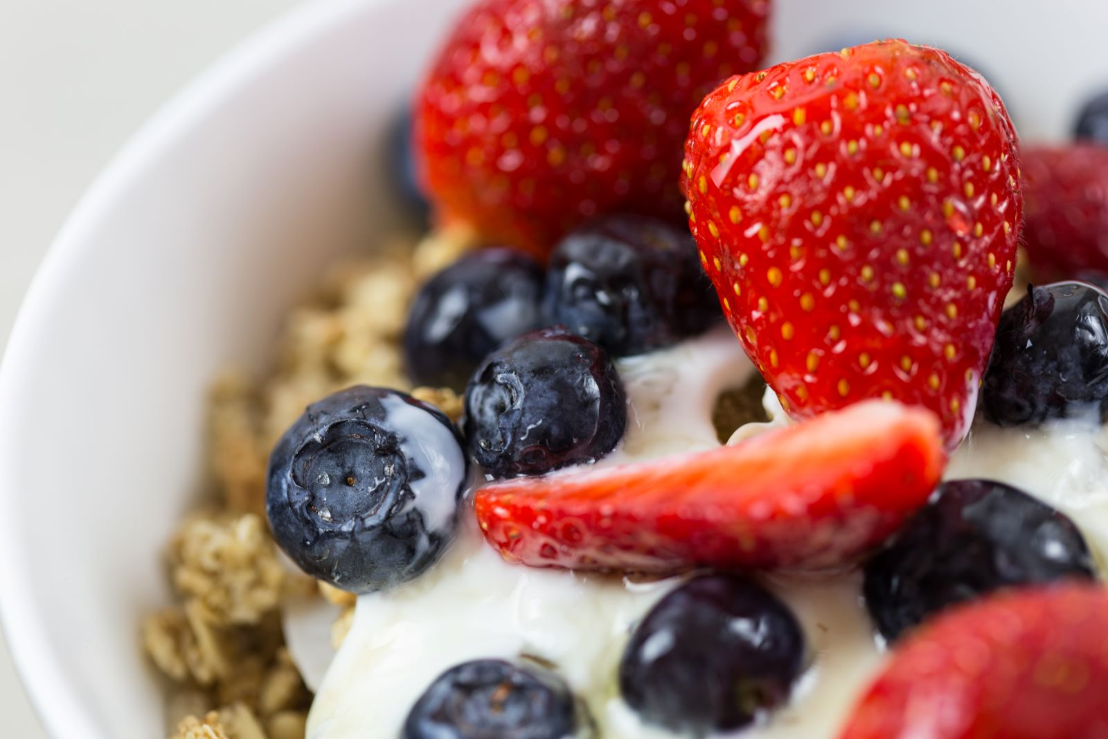 Bowl with yogurt parfait with strawberries and blueberries
