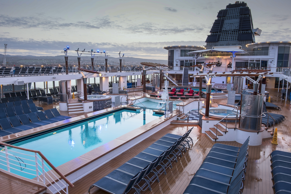 The deck of a Celebrity cruise ship with a pool and chairs