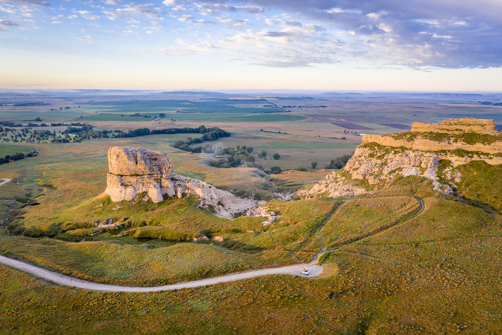 Courthouse and Jail Rocks in Gering Nebraska, the photo is from above overlooking the landscape, in the far distance farmland.  And Roads cutting through the rock formations.