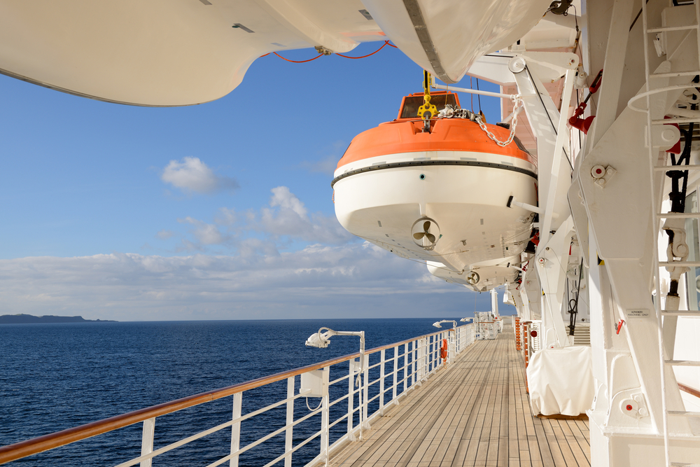 A cruise ship deck with a lifeboat, looking out to the sea