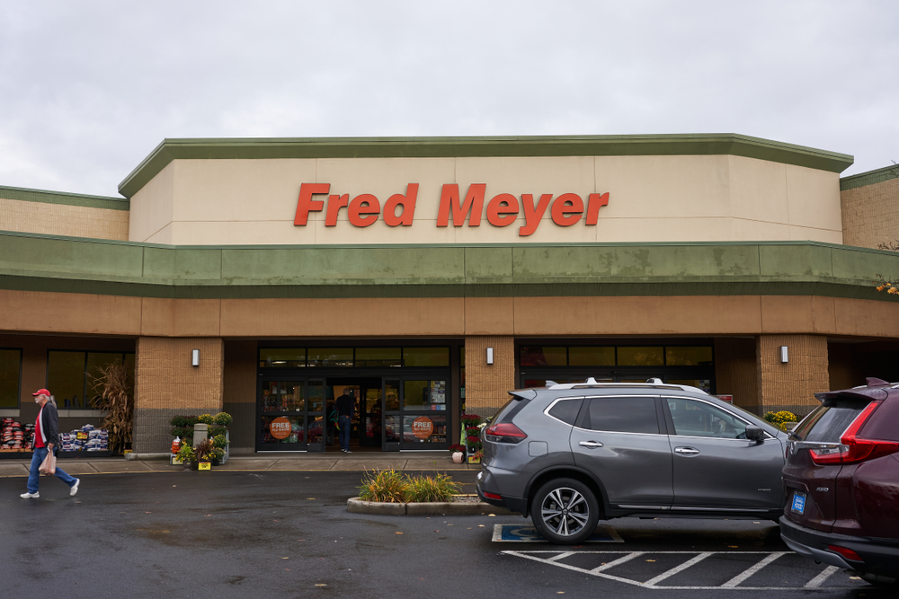 Fred Meyer grocery store car park with cars and a man walking