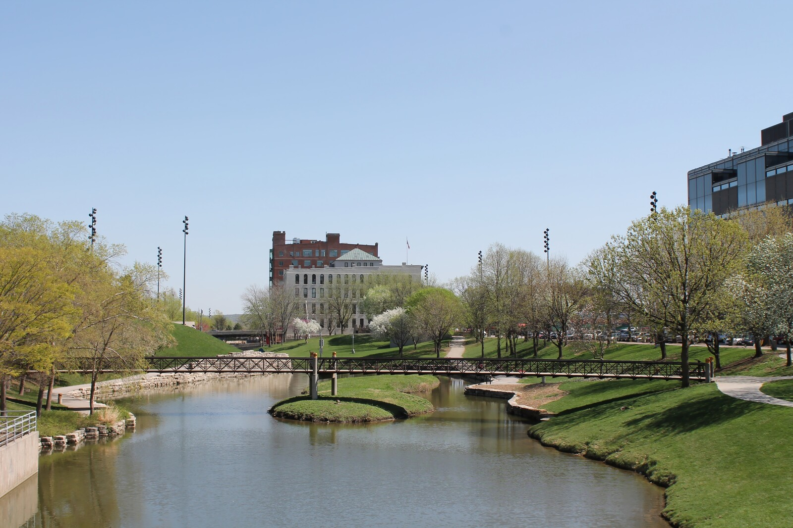 Best Places to Retire in Nebraska - Gene Leahy Pedestrian Mall in Omaha - Green grass lining the waterway with a footbridge over the water.
