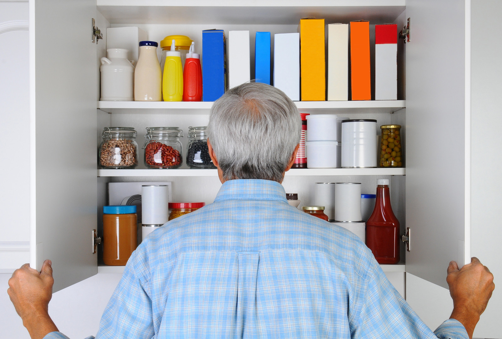 Senior standing in front of a cupboard full of food