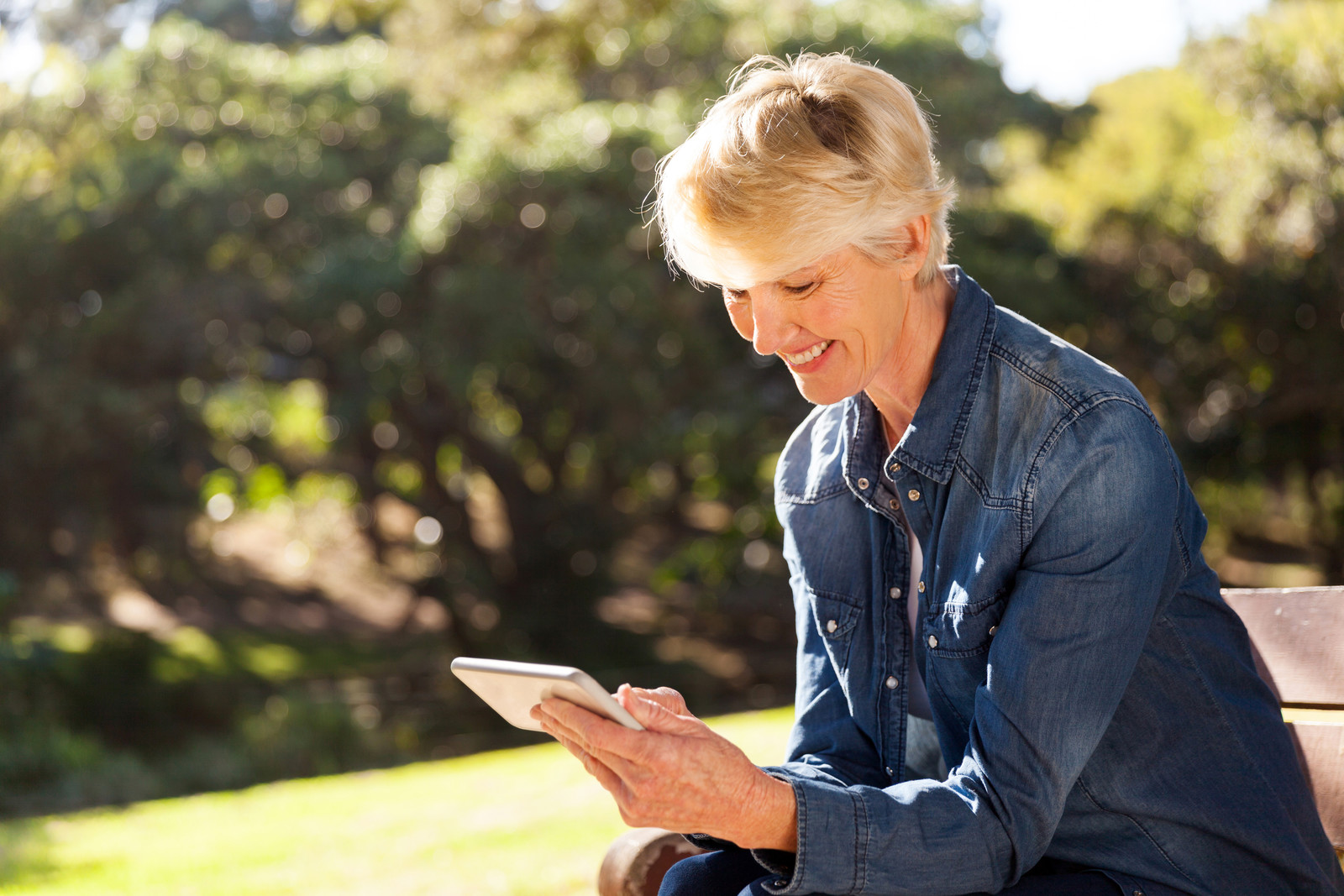 Blonde senior woman sitting on park bench looking at her phone smiling trees in the background.  No other people around