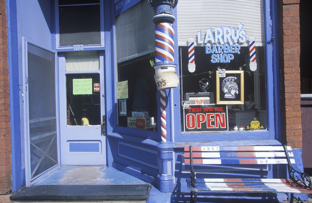 A blue exterior of a barber's shop in Salida Colorado, complete with barber's pole