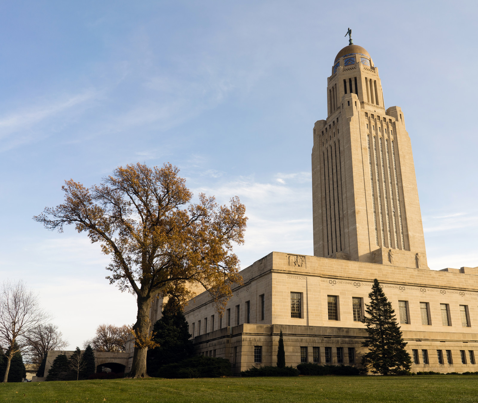 Lincoln Nebraska Capital Building with a dome on top. A few trees on the grounds, green grass and blue skies frame the building