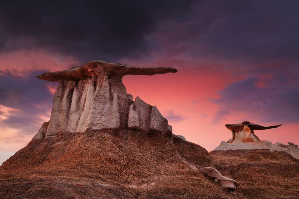 Best Places to Retire in New Mexico-Pink and purple New Mexico Sunset with rock formations decorating the landscape