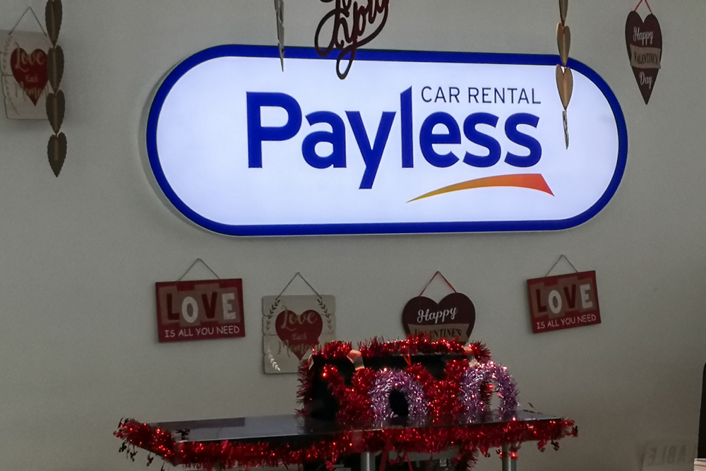 Payless Car Rental sign with various ornaments around it