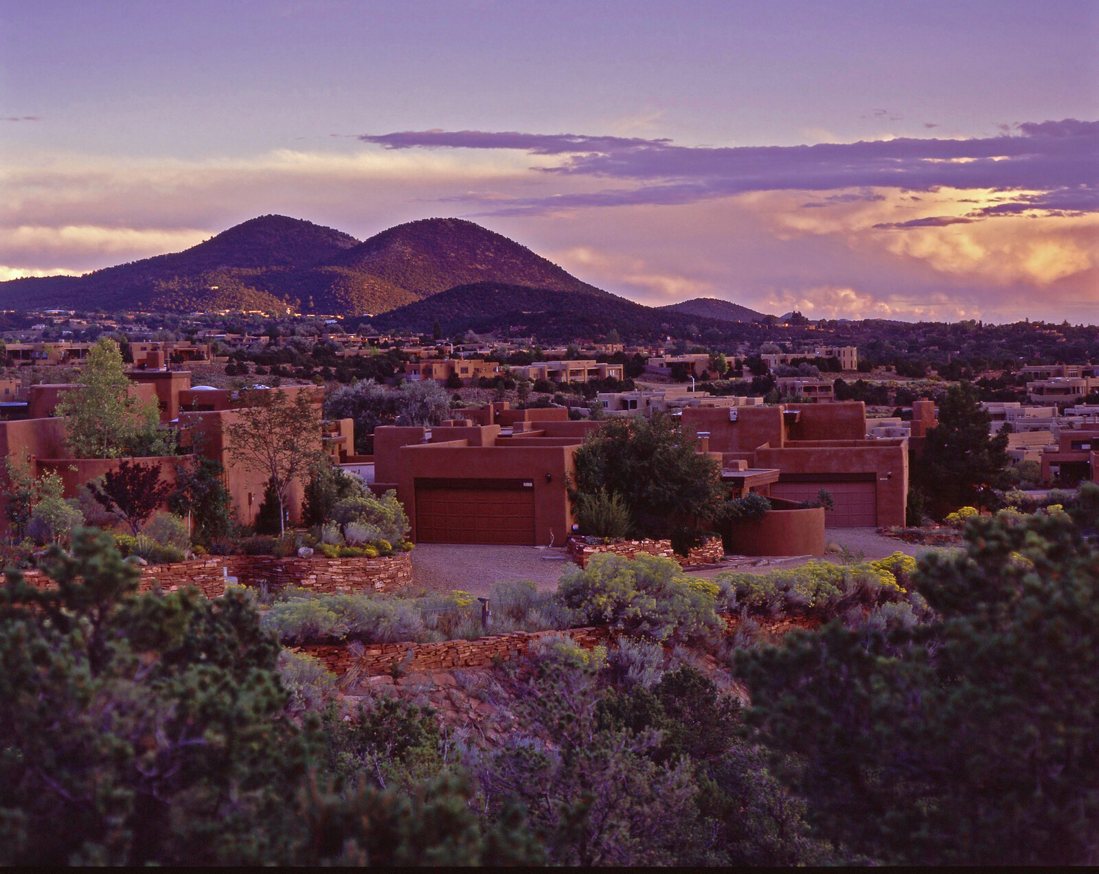 Sunset over the adobe style buildings in Santa Fe...with foot hills in the background