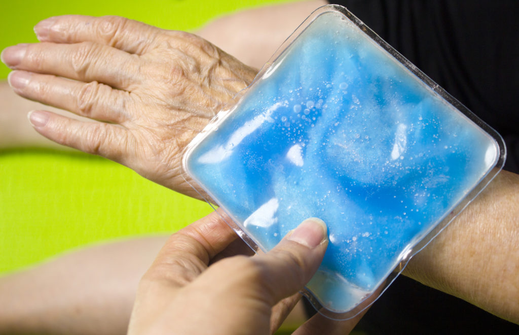 A senior woman uses an ice pack on her wrist.