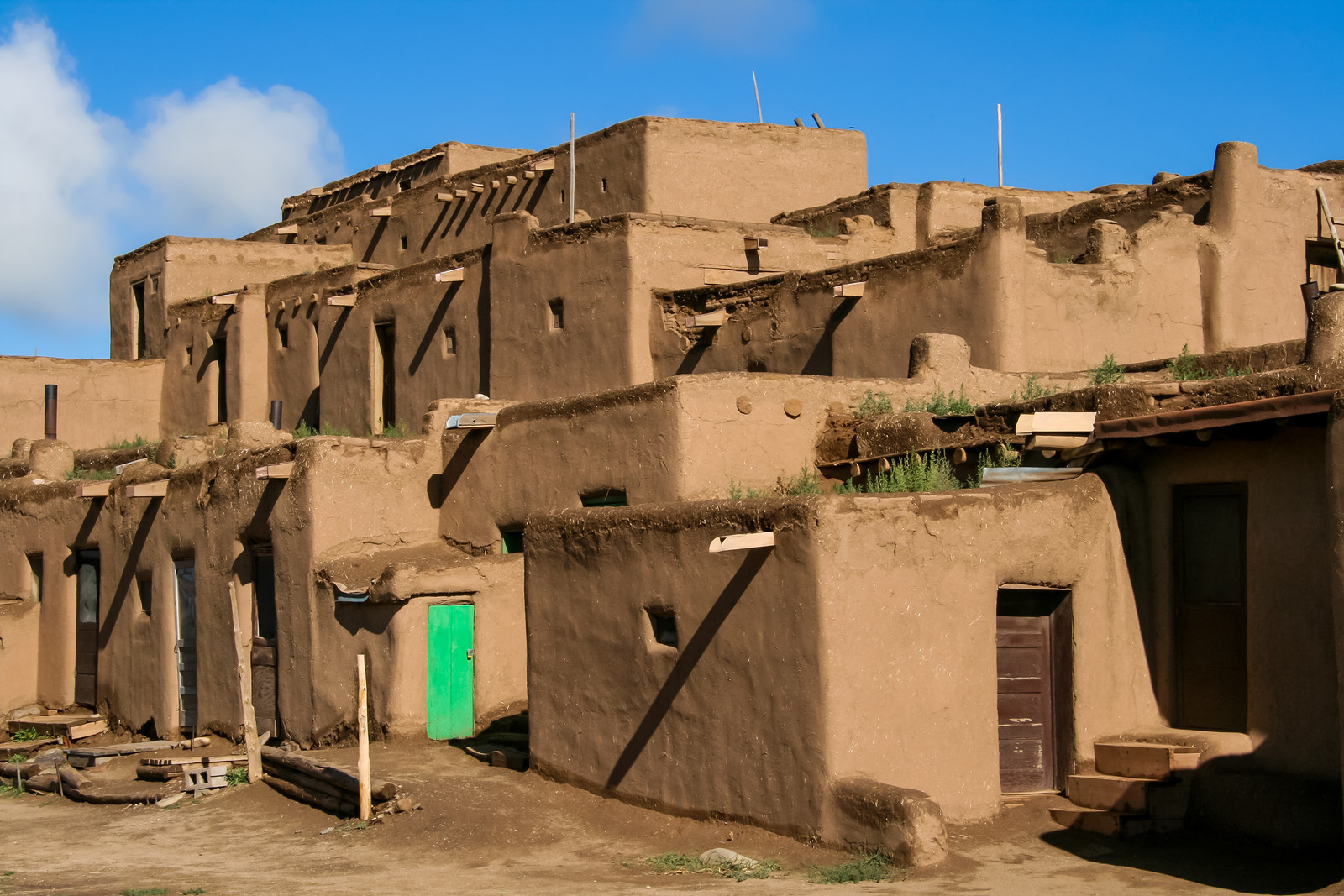 Pueblo housing in Taos, with a green door on one of the houses and blue sky in the background