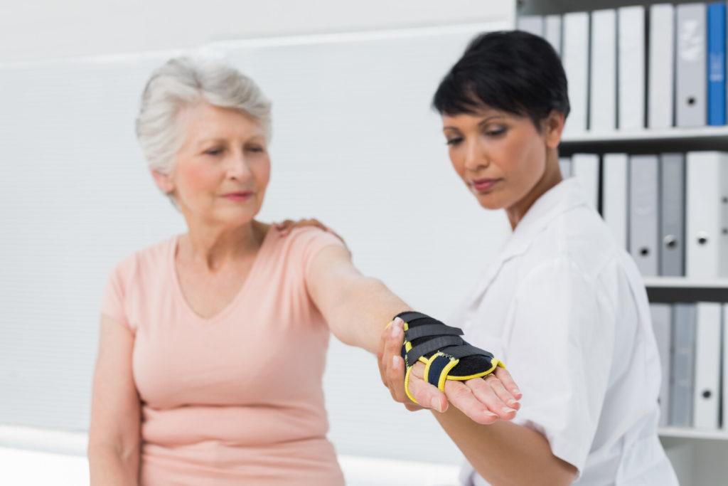 A doctor puts a wrist brace on a senior woman.