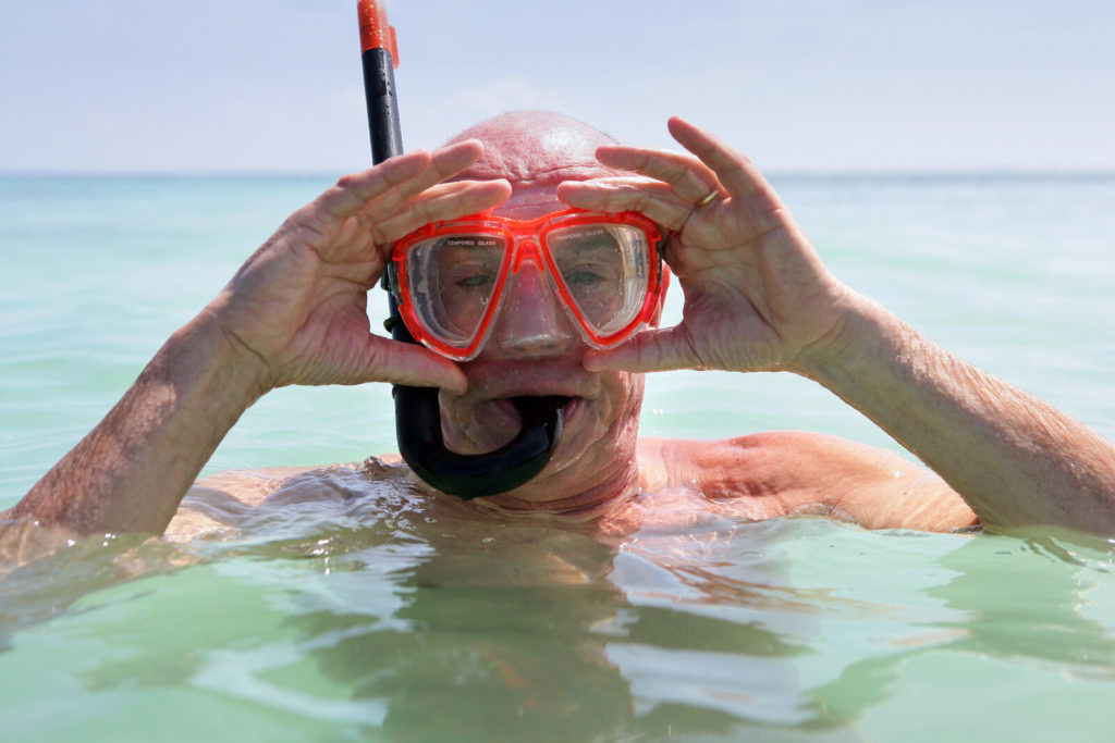 A senior man wears scuba gear and goggles.