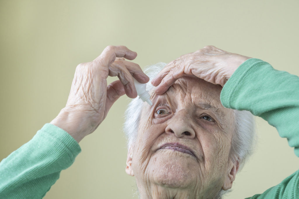 A senior woman uses eye drops.