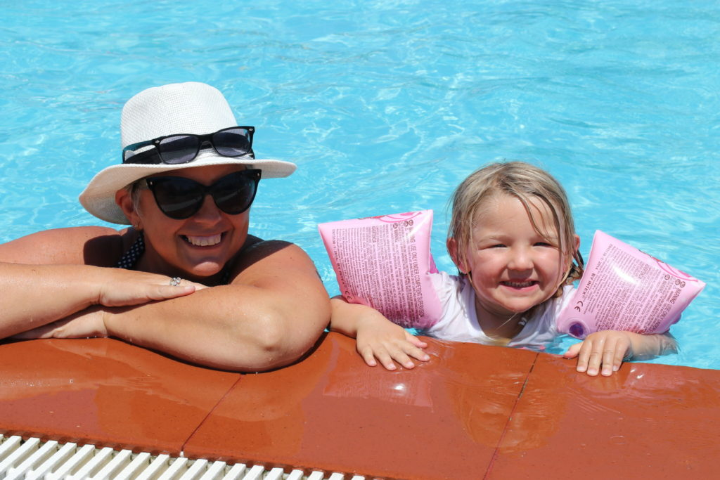 A grandmother and granddaughter in a pool on vacation.