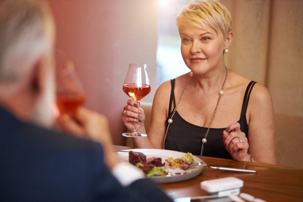 A senior couple enjoys a fine dining meal.