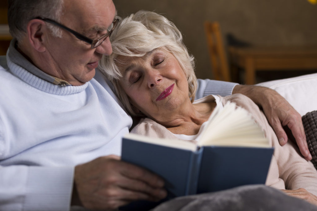 A senior couple rests on the couch together.