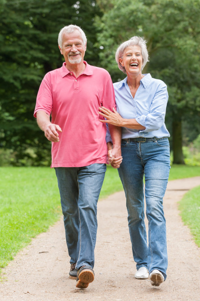 A senior couple walks together.