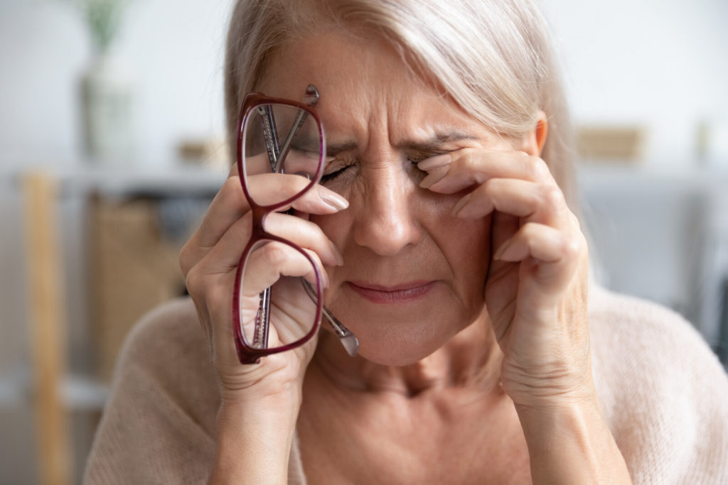 A senior woman holds her glasses while she touches her eyes in visible pain.