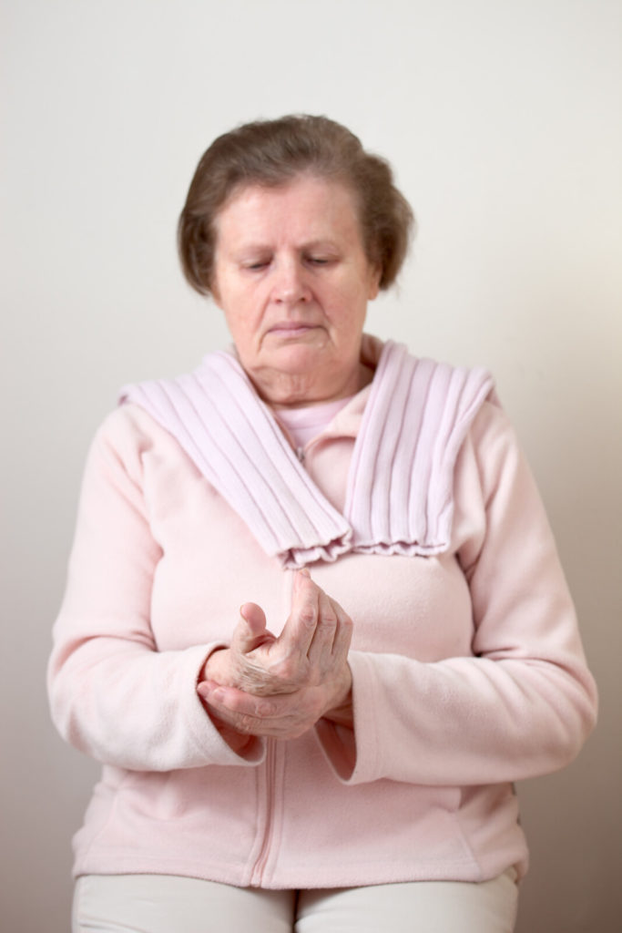 A senior lady wearing a sweater holds her aching wrist.