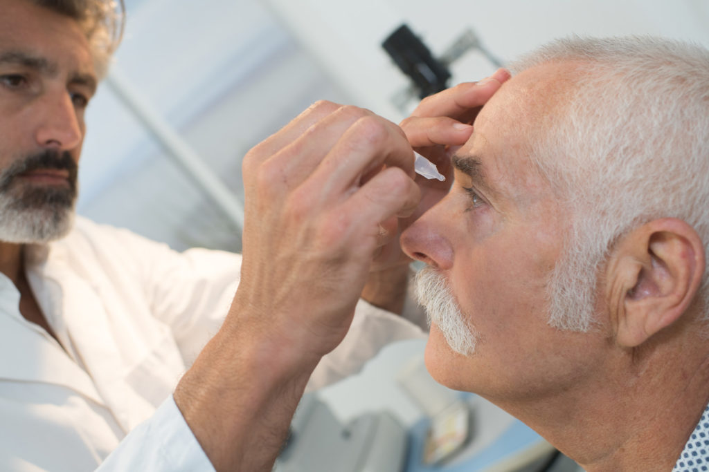 A senior man gets eye drops from a doctor.