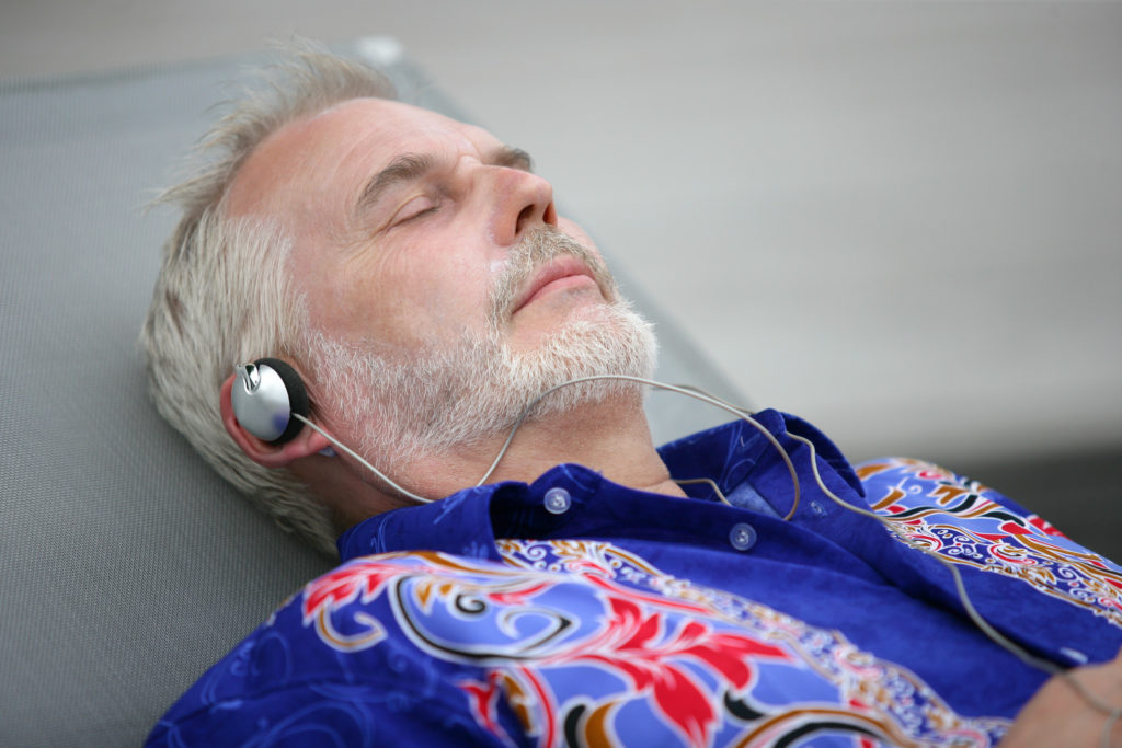 A senior man listens to music and relaxes.