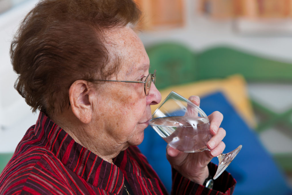 A senior woman drinks from a glass of water.
