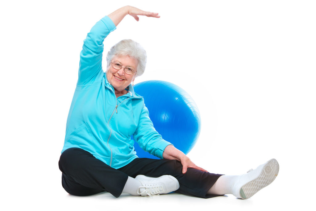 A senior woman does stretching exercises.