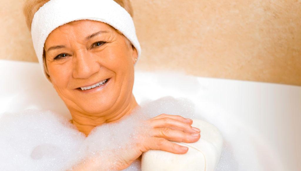 A senior woman takes a bath.