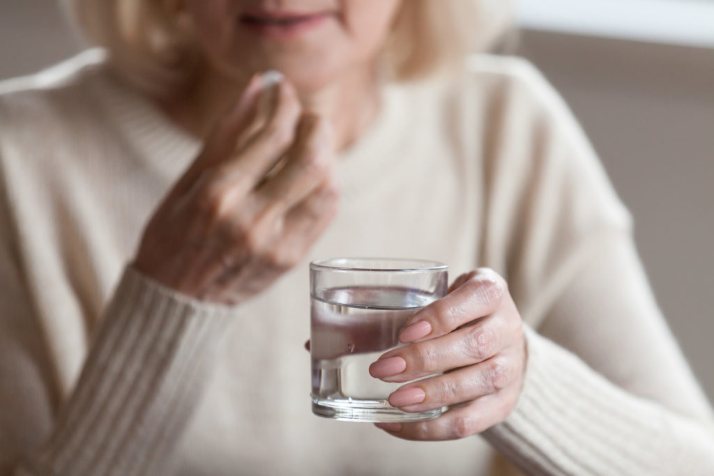 Senior woman taking pill.