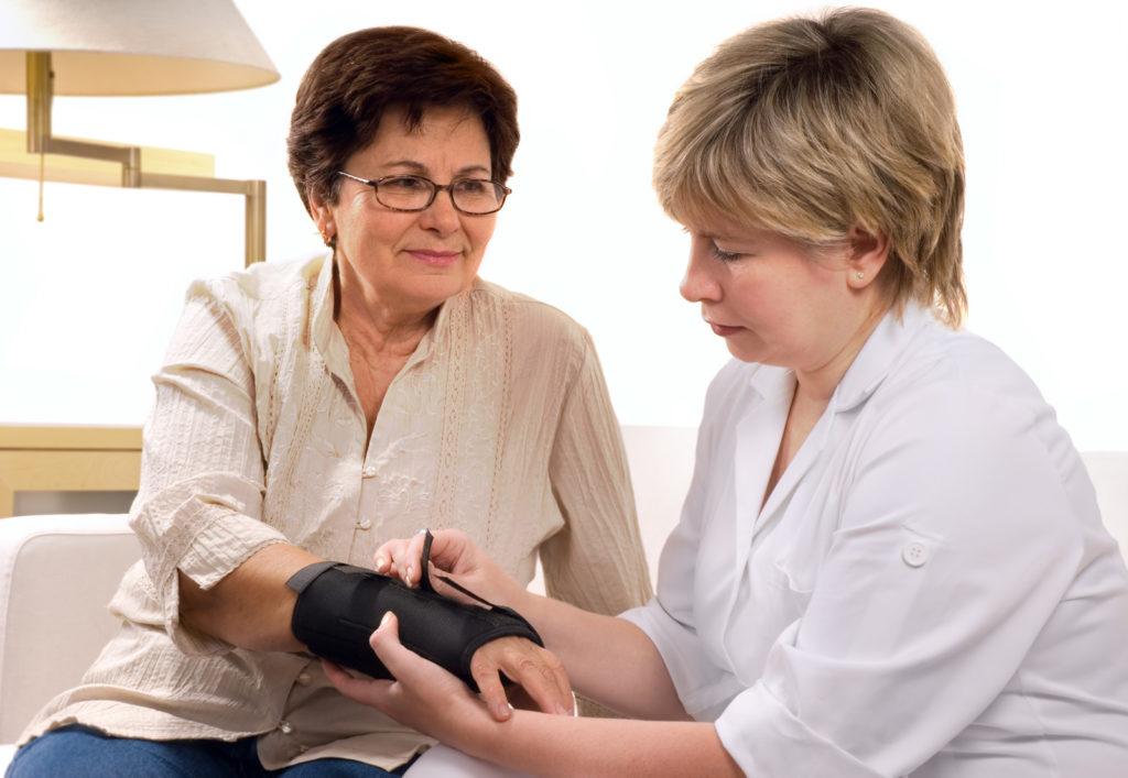 A senior woman wears a wrist brace.