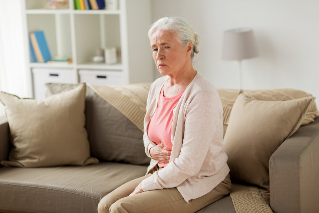A senior woman sitting on the couch holds her stomach in pain.