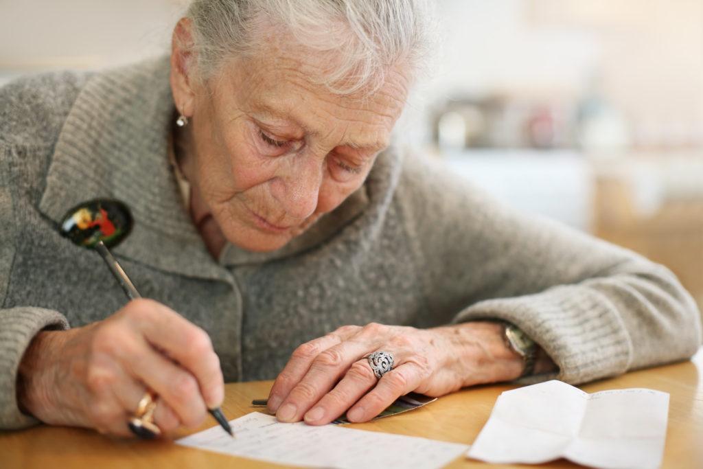 A senior woman is writing down something.