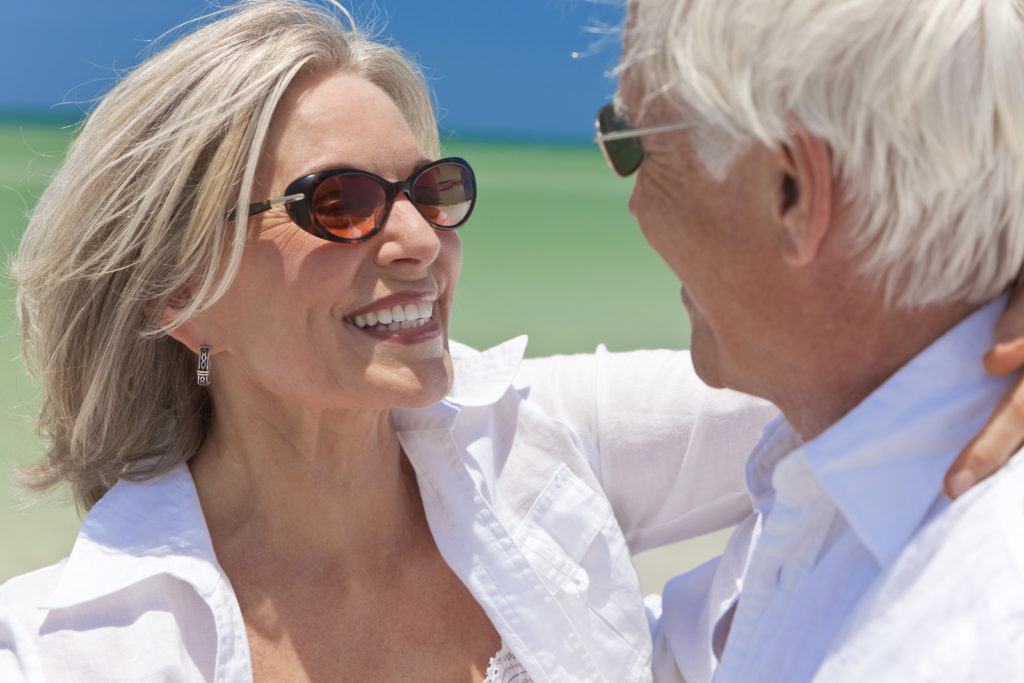 Senior man and woman wearing sunglasses on the beach.