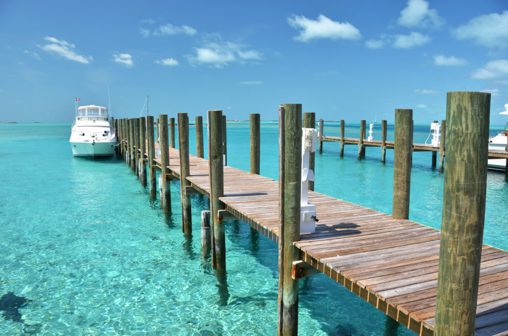 A long dock is over beautiful blue water in The Bahamas.
